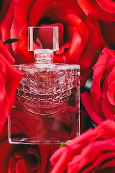 高級ギフトの美しさのフラットレイの背景と化粧品としての夏の香水の赤いバラと香水...