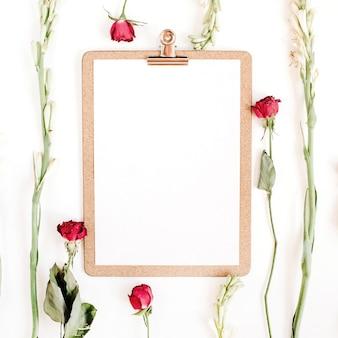 白い表面にクリップボードと赤いバラと白い花のフレーム