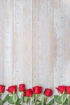 Красные розы внизу деревянной стены макет открытки-приглашения на день святого валентина