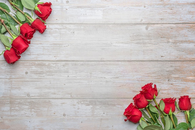 Красные розы по углам деревянной стены макет открытки-приглашения на день святого валентина