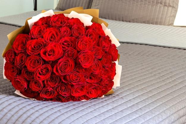 Большой букет красных роз на кровати. концепция дня святого валентина. романтическое утро.