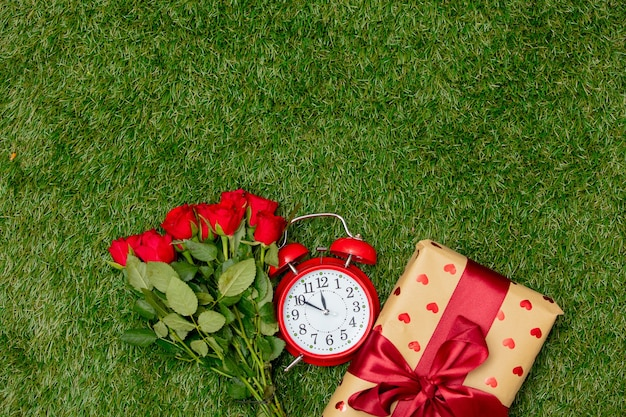 Red roses bouquet and gift box with alarm clock on green grass.