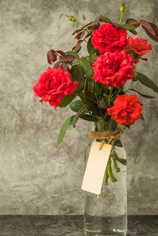 Red roses bouquet in the glass bottle with blank tag