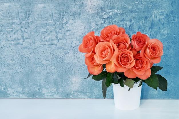 파란색 배경에 흰색 꽃병에 빨간 장미 꽃다발