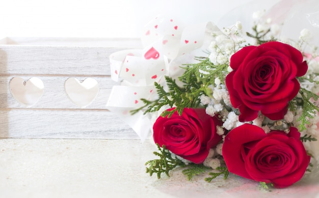 Red roses bouquet and white wooden box with hearts background