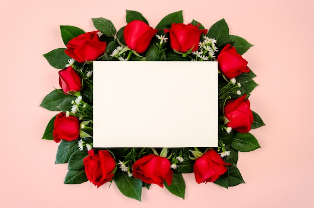 Red roses bouquet with blank white paper card.