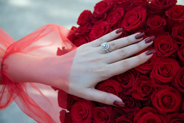 Red roses bouquet with engagement ring. bride with flower bouquet and engagement ring.