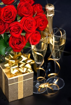 Красные розы, шампанское и золотой подарок на черном фоне. праздничное украшение