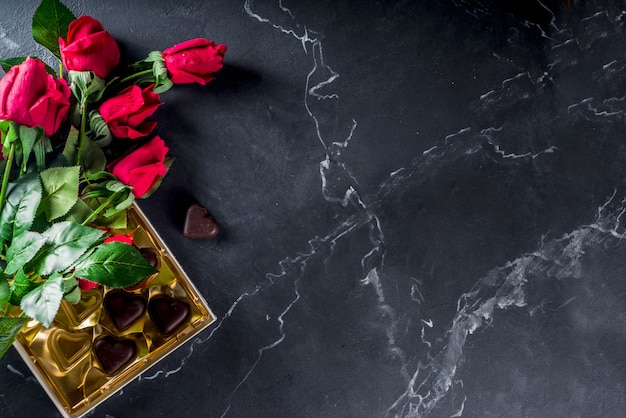 Red roses and chocolate hearts on marble floor