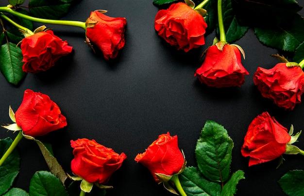 Красные розы, концепция дня святого валентина на черном столе, вид сверху.