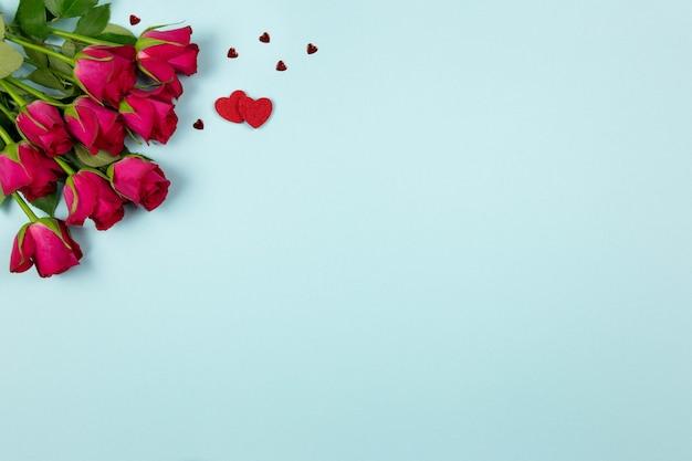Красные розы, цветы и конфетти сердца на пастельно-голубой поверхности