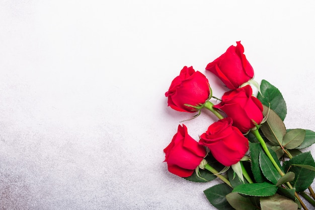 Red roses flowers on stone background. valentine's greeting card. top view. copy space