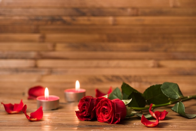 Red roses flowers with burning candles