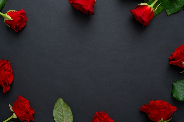 Red roses frame on a black background, copy space.
