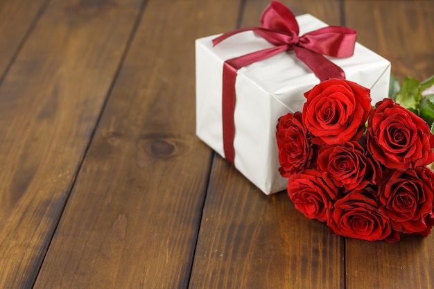 Red roses and gift box on brown wooden table