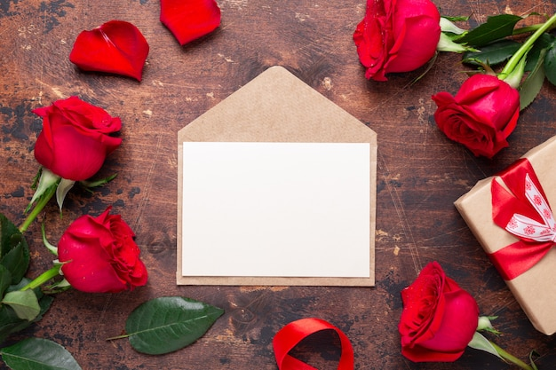 Red roses, gift box and envelope on wooden background