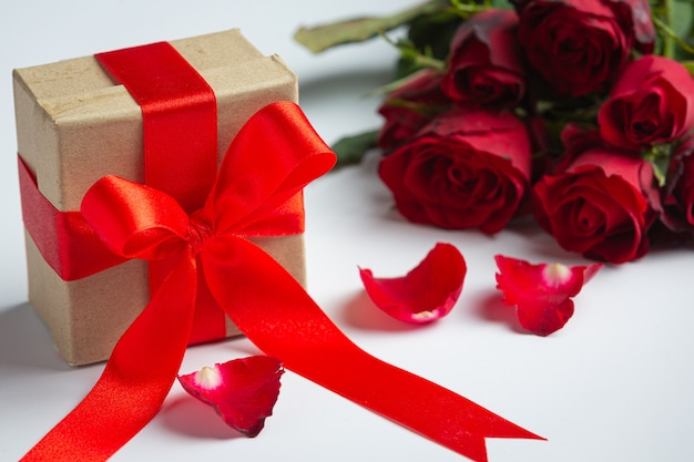 Red roses and gift box on marble background
