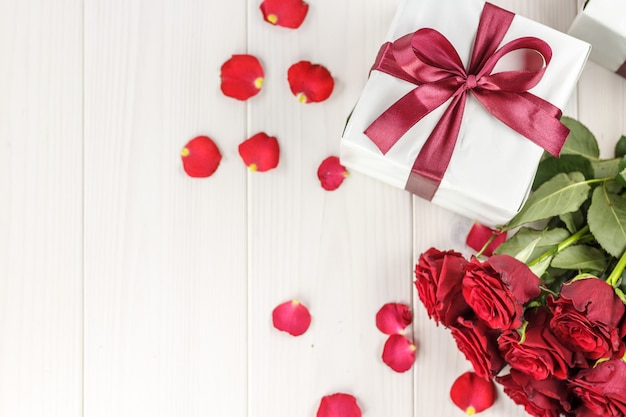 Red roses and gift box on white wooden table, top viewed