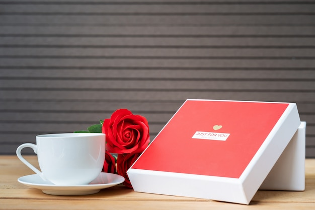 Red roses and gift box with coffee cup on wooden table