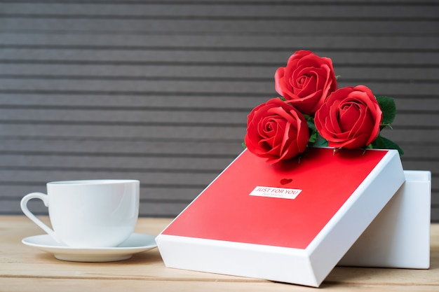Red roses and gift box on wooden table
