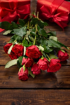 Red roses, gift boxes, linzer cookies on a dark wooden