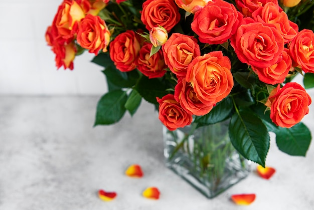 Red roses in a glass vase on the table