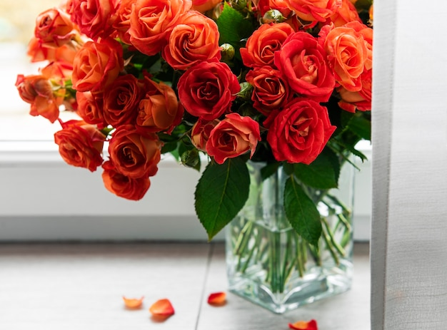 Red roses in a glass vase on the window sill