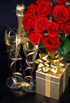 Red roses golden gift and and champagne on black background