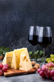 Red roses, grapes, cheese and a glass of red wine on a black concrete background