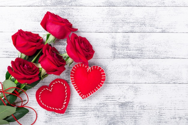 Red roses and hand made hearts on wooden white background. the concept of valentine day. copy space for your text