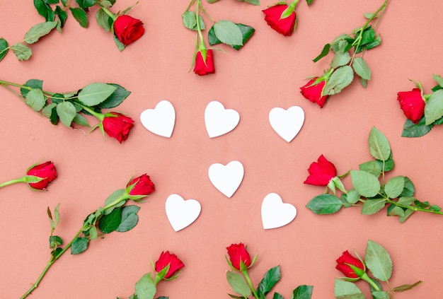 Red roses and heart shapes on pink