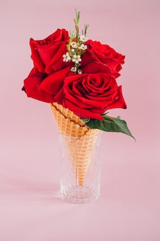 Red roses in ice cream on pink, copy space