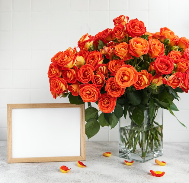 テーブルの上に空のフォト フレームを持つガラスの花瓶に赤いバラ