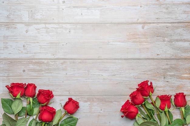 Красные розы в букетах на нижней части деревянной стены postc приглашения на день святого валентина 14 февраля