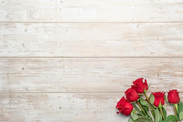 Красные розы в букетах деревянная поверхность макет для открытки