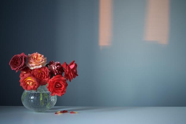 Красные розы в стеклянной вазе на синем фоне