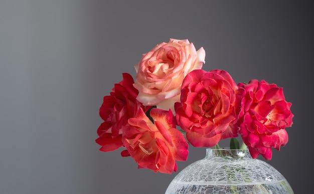 Красные розы в стеклянной вазе на сером фоне