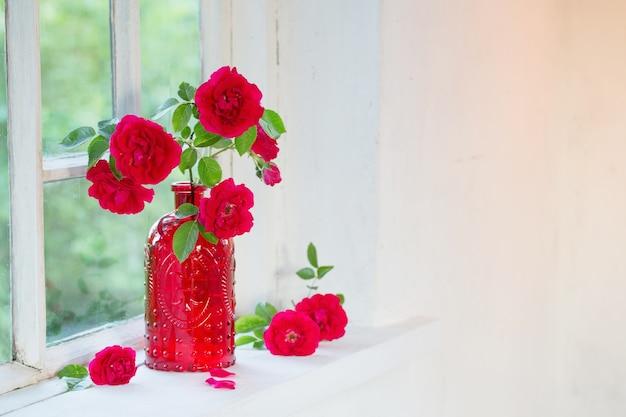 Красные розы в красной стеклянной вазе на подоконнике