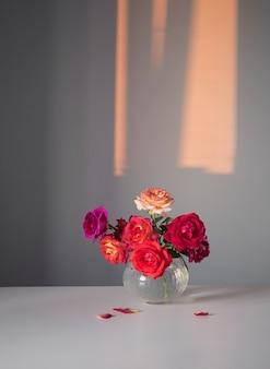 灰色の背景に白い花瓶の赤いバラ