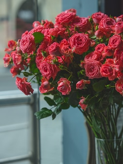 Red roses inside transparent glass vase in a room .