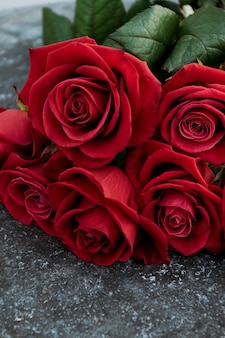 コンクリートの背景に赤いバラ