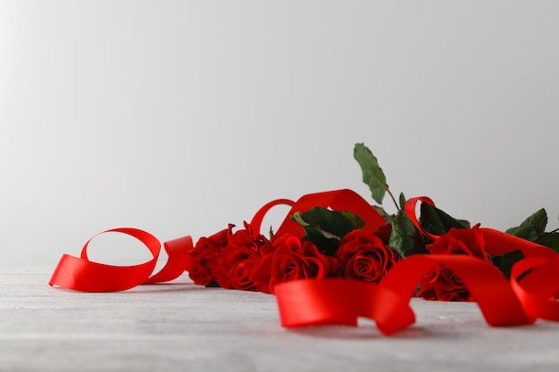 Красные розы на столе с лентой