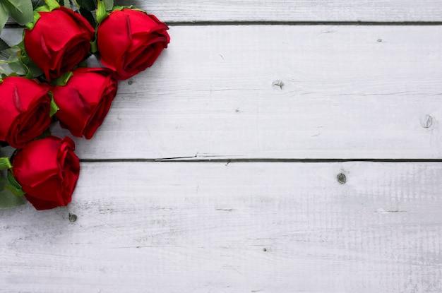 발렌타인과 웨딩 프레임 개념에 대 한 텍스트 복사 공간 흰색 나무 배경에 빨간 장미.