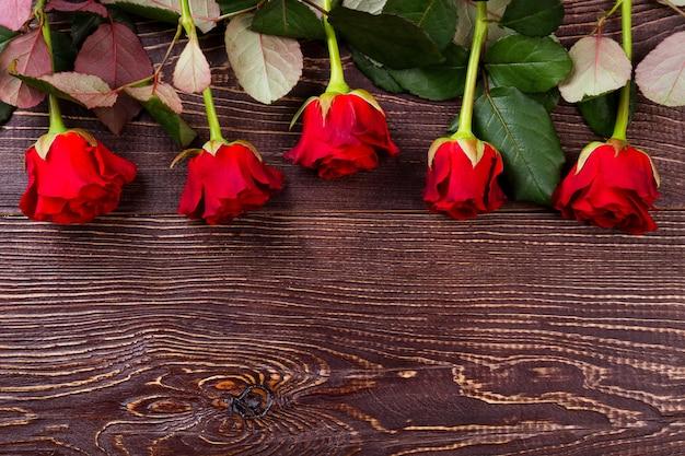 나무 바탕에 빨간 장미입니다. 꽃과 잎. 사랑의 상징으로 장미. 항상 즐거운 놀라움.