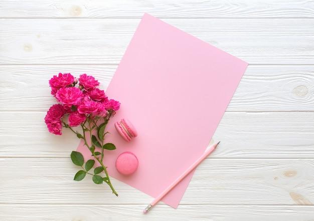 赤いバラ鉛筆マカロンと木製の背景に空白のピンクの紙カード