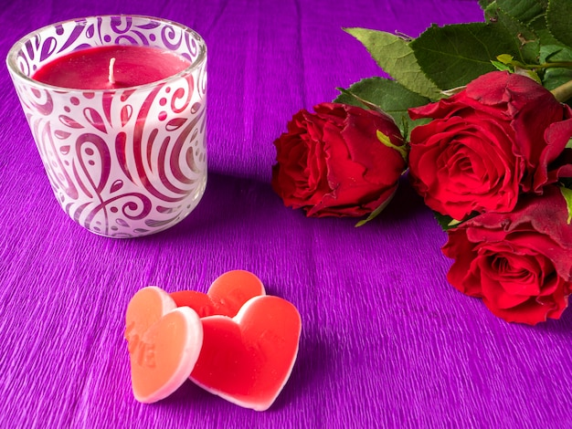 Red roses next to red candle and red hearts on purple