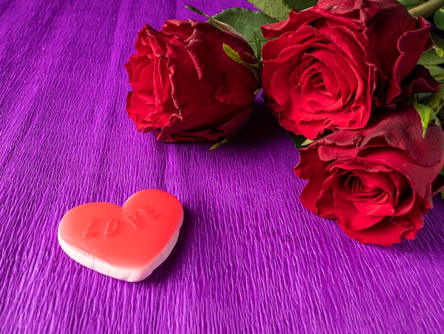 Red roses and red heart on purple