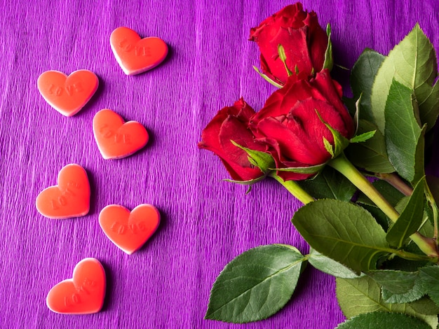 Red roses and red hearts on purple