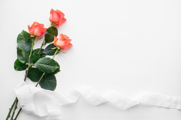 Red roses and ribbon on white table