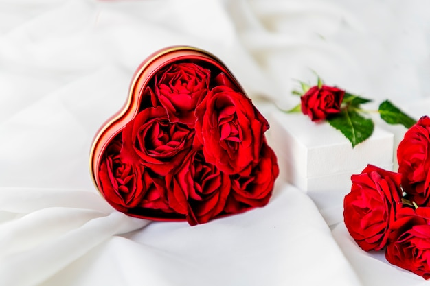 Red roses in the shape of a heart on white silk fabric. congratulation on valentine's day.
